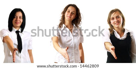 A team of young pretty businesswomen holding their hands out for handshaking. They are smiling and they are wearing elegant white shirts. - stock photo