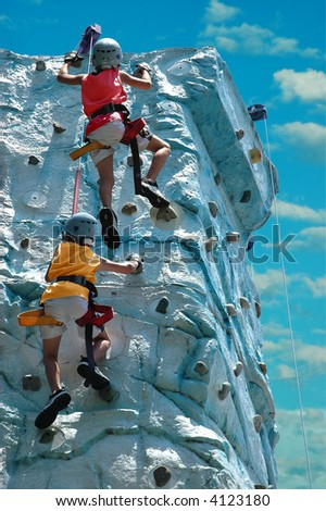 A team (two kids) climbing the top of a rock wall - stock photo