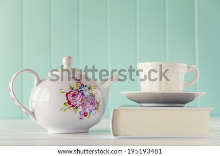 A teapot and a tea cup on a white book. A white wooden table with a robin egg blue background. Vintage style. - stock photo