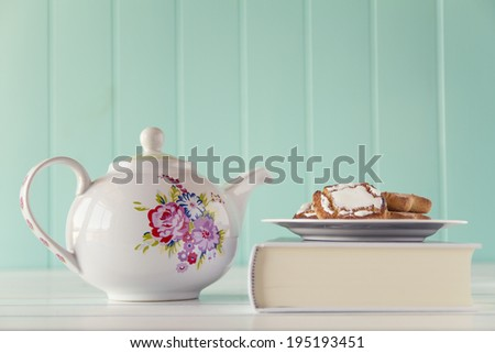 A teapot and some cookies on a plate on a white book. A white wooden table with a robin egg blue background. Vintage style. - stock photo