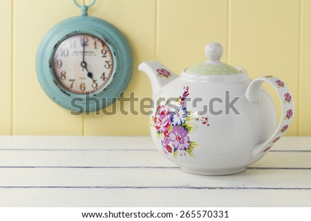 A teapot on a white wooden table. In the background a turquoise clock on a yellow wainscot. Vintage tea time - stock photo