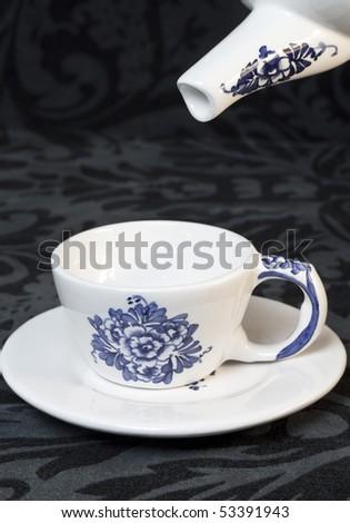 A teapot pouring tea in teacup - stock photo