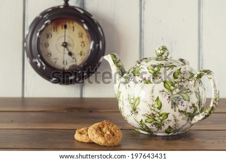 A teapot, two german cookies and a clock in the background. A wooden table with a white background. Five o'clock. Tea time. Vintage style. - stock photo