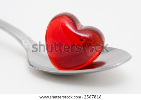 A teaspoon with sits extended with a red glass heart on the spoon.  Perfect illustration for the saying a spoonful of love or even a little sugar makes the medicine go down easier. - stock photo