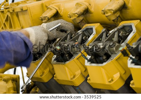 A technician performing periodic engine maintenance in a landfill gas recovery plant - stock photo