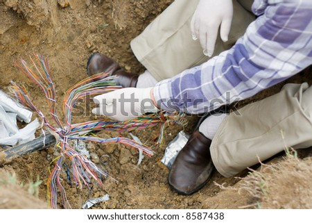 a technician repairs an underground telephone line - stock photo