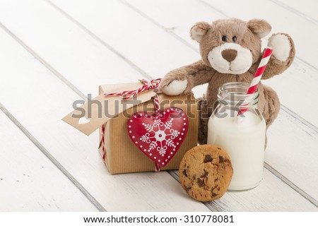 A teddy bear, a red heart and a school milk bottle with a straw on a white wooden table. A paper parcel (christmas gift box) wrapped with paper kraft and tied with red & white baker's twine. - stock photo