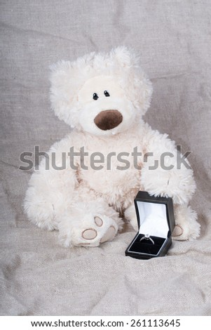 A teddy bear holding a box with a ring with diamont