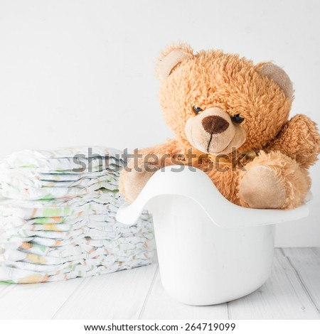 A teddy bear in a white potty next to stack of diapers. Conceptual image representing potty training - stock photo