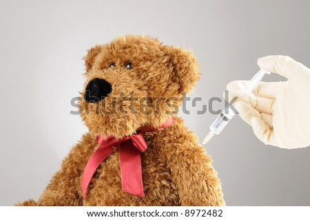 a teddy bear is getting an injection - stock photo