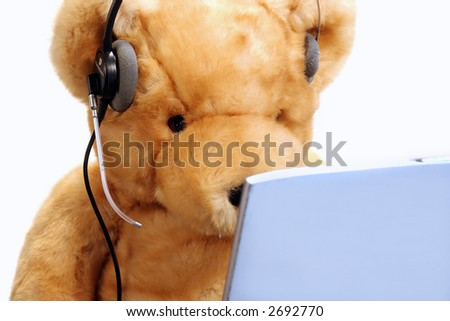 A teddy bear prepared for customer service or to chat on the phone or online. - stock photo