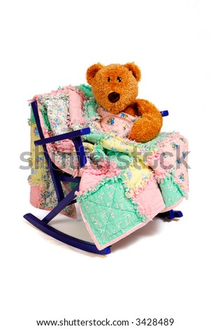 A Teddy Bear sits in a vintage child's chair,  comforted with a rag quilt. - stock photo