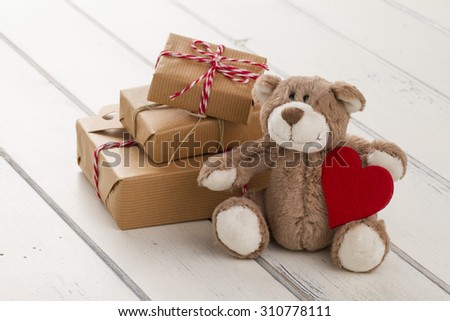 A teddy bear sitting with a red heart. Some paper parcels (christmas gift boxes) wrapped with paper kraft and tied with red & white baker's twine on a white wooden table - stock photo