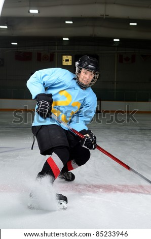 A Teen Age Hockey Player Makes Sharp Stop in the Rink - stock photo