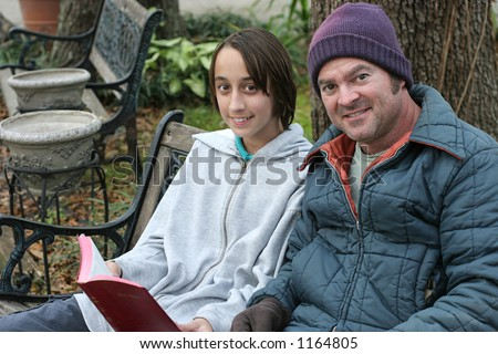 A teen-aged boy reading the sharing the bible bible with a homeless man. - stock photo