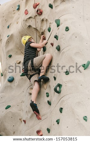A teen boy climbing on a rock climbing wall with safety harness and helmet on. - stock photo