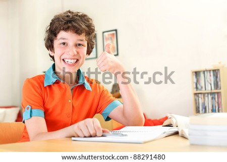 A teen boy gives a happy thumbs up to education as he studies at home. - stock photo