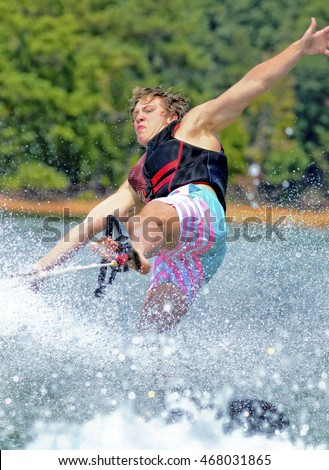 A teen boy holding the rope with his foot and trying to keep his balance on a trick ski.