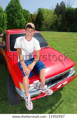 A teen boy proudly sitting on his truck. - stock photo