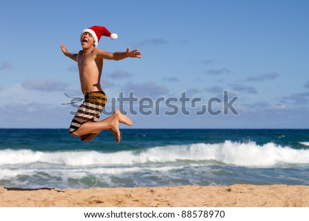 A Teen Boy Wearing a Santa Hat Jumping on the Beach in Hawaii - stock photo