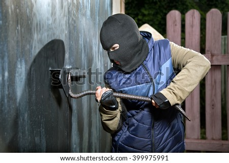 a teen-burglar breaking open of a padlock metal door - stock photo
