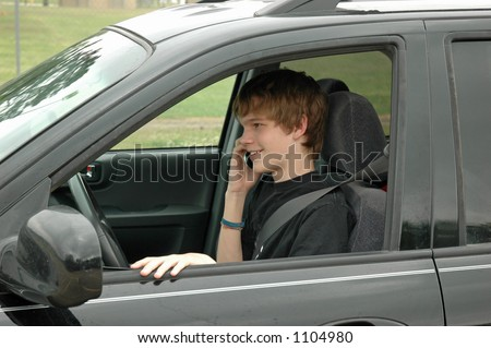 A teen driver sits on the side of the road in his parent's SUV and talks on his cell phone - stock photo