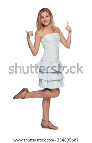 A teen girl holds her thumbs up against the white background - stock photo