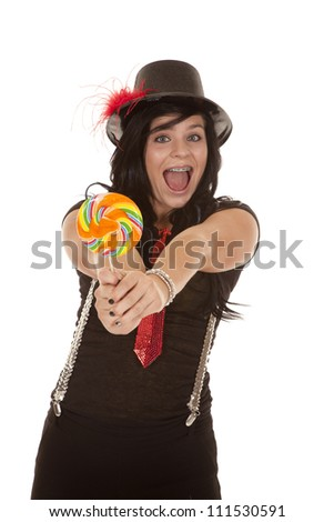 A teen girl in her jazzy outfit holding out a colorful sucker with a big smile on her face. - stock photo