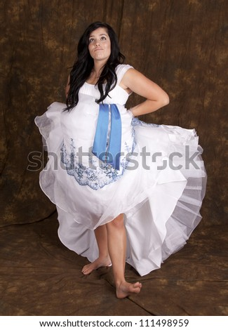 A teen girl in holding up her dress and showing some attitude. - stock photo
