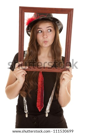 A teen girl showing her fun side by holding up a picture frame with a pucker on her lips. - stock photo