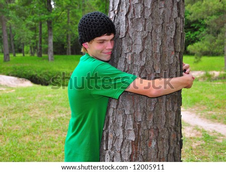 A teen in a green tee shirt hugs a tree in the forest - stock photo