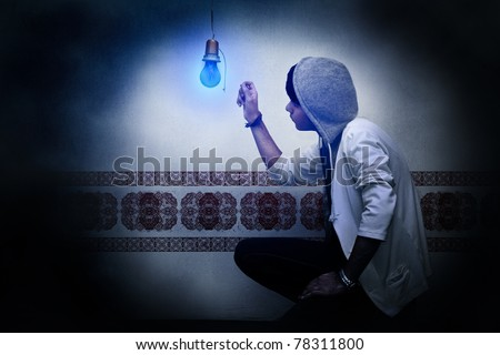 A teen reaching a dark blue bulb, on grungy and vintage look background. - stock photo