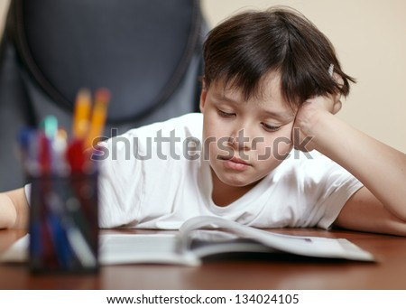 A teen school boy studies hard over his book at home as he props his head up with his arm. - stock photo