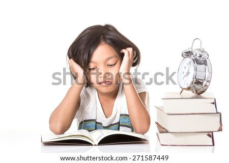 A teen school girl studies hard over her book at home as he drops his head up with her arm. - stock photo