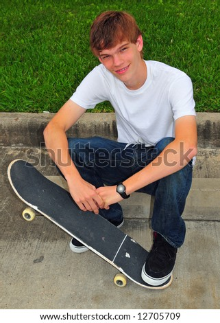 A teen sits on the curb and rests with his skateboard - stock photo