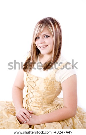 A teen sitting in her gold formal with a big smile on her face.