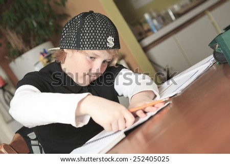 A teen working on his homework in the kitchen table.