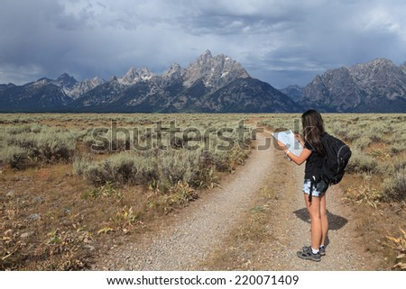 A teenage Asian girl reading a map in the Grand Teton National Park, Wyoming, USA - stock photo