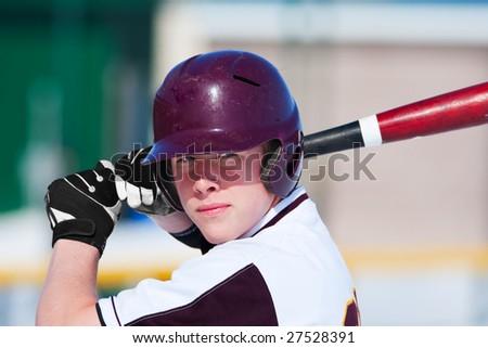 A teenage baseball player ready to bat. - stock photo
