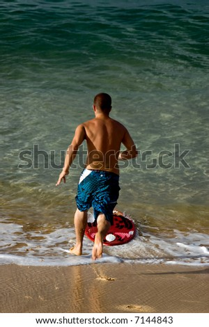 A teenage boy at the beach running to jump onto a boogie board - stock photo