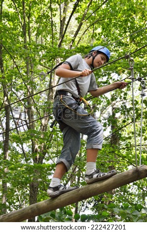 A teenage boy is climbing on the strung log at the rope obstacle course high up. He is photographed against the forest. - stock photo