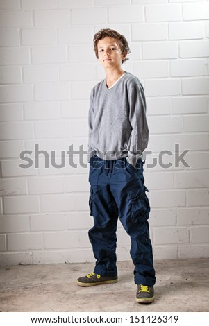 A Teenage boy, standing, hands in his pocket, making a cool confident face and pose. - stock photo