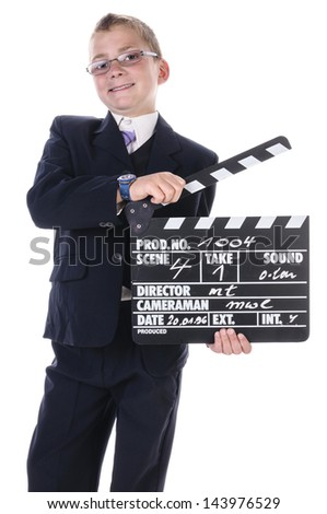A teenage boy wearing a dark suit and tie, holding a clapper board in hand and laughing at the camera - stock photo