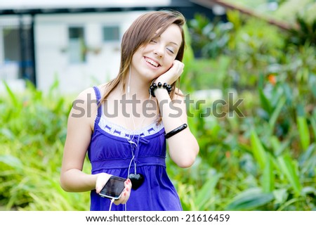 A teenage girl chilling out to music in her garden