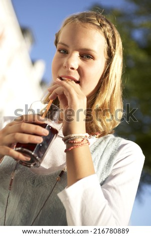 A teenage girl drinking. - stock photo