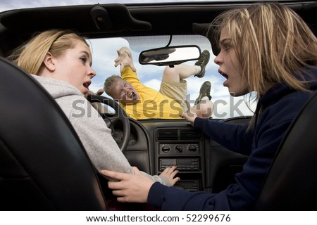 A teenage girl driving and playing with the radio while her friend is showing that she just hit someone because she was distrated by the radio. - stock photo