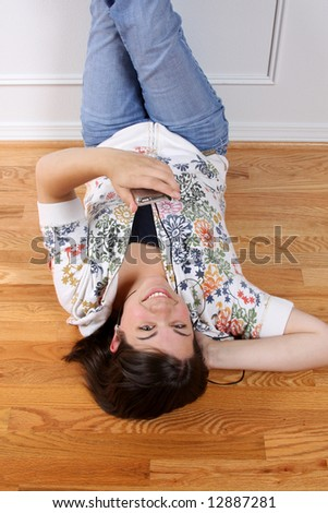 A teenage girl hanging out and listening to music on headphones. - stock photo