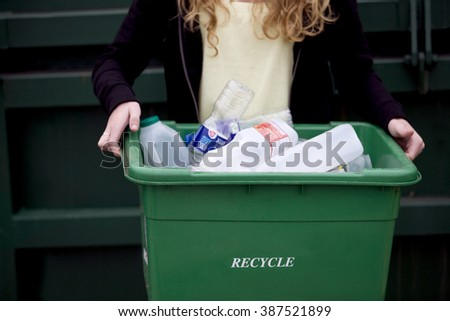 A teenage girl holding a recycling container - stock photo