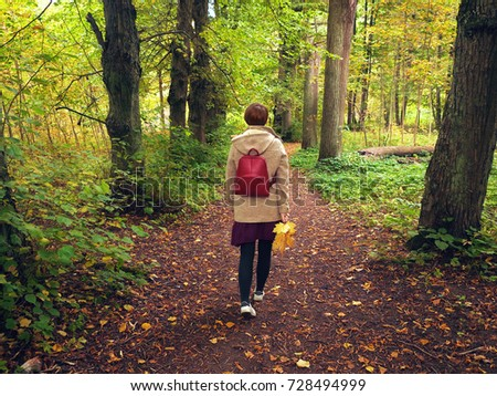 a teenage girl in a beige coat with a hood and a red backpack is walking along the autumn park along a path strewn with yellow foliage.