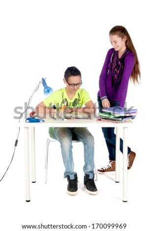A teenage girl is helping a teenage boy with his homework - stock photo